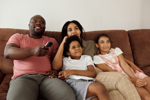 family sitting on a brown couch watching TV
